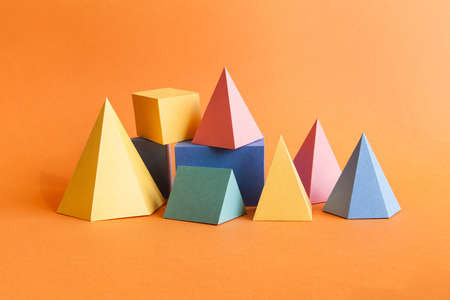 Colorful abstract geometrical composition. Three-dimensional prism pyramid rectangular cube objects on orange paper background. Yellow blue pink green colored solid figures, soft focus photo. Stock Photo