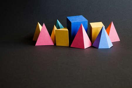 solid figure: Colorful astratto figure solide geometriche su sfondo nero. cubo rettangolare giallo blu rosa figure prisma piramide colore verde. carta ruvida nero, profondità di campo, spazio copia. Archivio Fotografico