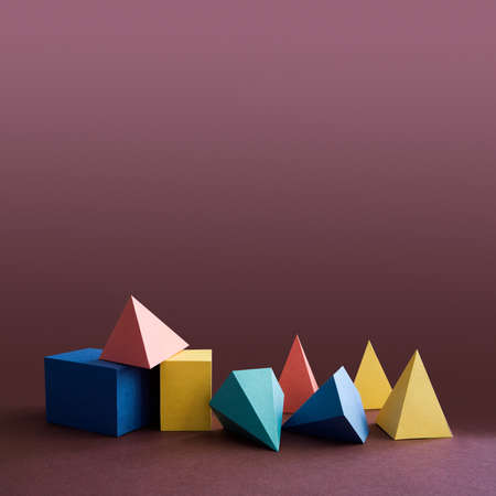 solid: Colorful platonic solids, abstract geometric figures on violet background. Pyramid prism rectangular cube yellow blue pink green colored shapes. Shallow depth of field, copy space Stock Photo