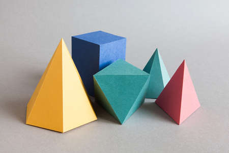 Colorful platonic solids, abstract geometric figures on gray background. Pyramid prism rectangular cube yellow blue pink green colored shapes. Shallow depth of field, copy space