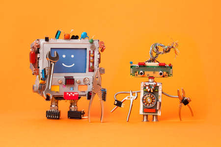 Robots friends ready for service repair. Funny robotic characters with instrument, pliers hand wrenches. Smile message blue screen monitor, cyborg electric wires hairstyle, circuits. Orange background. Standard-Bild