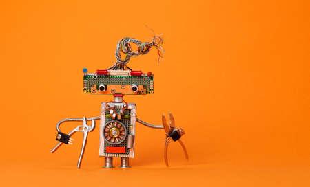 alicates: Robot divertido electricista con alicates. Juguete robótico del diseño creativo con el peinado de los alambres eléctricos, circuitos electrónicos, condensadores del vintage de los condensadores del microprocesador. Texto de copia de fondo naranja. Foto de archivo