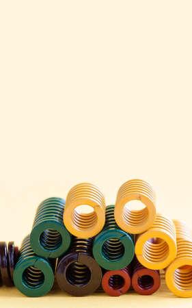 coil: Muelles metálicos con diferentes tamaños de flexibilidad de dureza. Espirales de acero de colores bobina cables sobre fondo amarillo. Copie el espacio. Foto de archivo