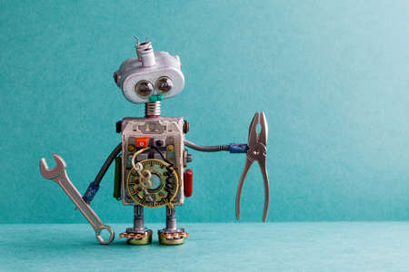 Robot di elettricista di design creativo con pinze per chiavi a mano. Divertente giocattolo meccanico carattere lampadina testa occhi, fili elettrici, resistenze vintage condensatori. Testo della copia del fondo del Libro Verde Archivio Fotografico - 76403740