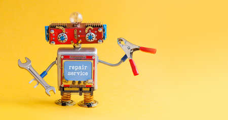 Repair service robot handyman master with hand wrench red pliers. Creative design smiley cyber toy character ready for maintenance fix work. Yellow paper background copy space for your design. Stock Photo