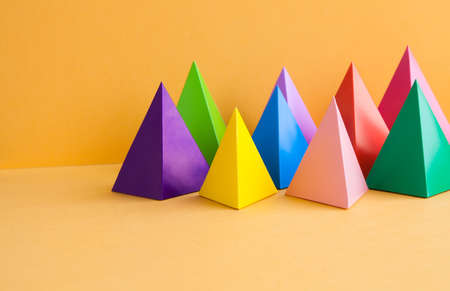 Colorful geometric abstract still life composition. Bright prism pyramid triangle shape figures. Violet yellow blue pink green red color objects, orange paper background. Stock Photo