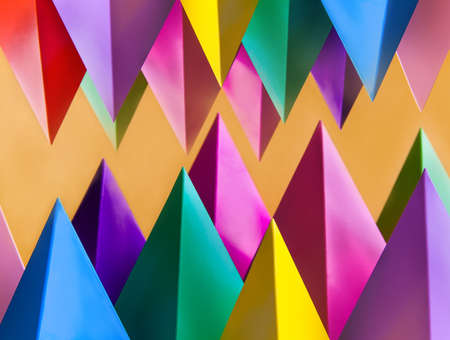 Abstract colorful geometric pattern with prism pyramid triangle shape figures. Yellow blue pink green violet red colored objects
