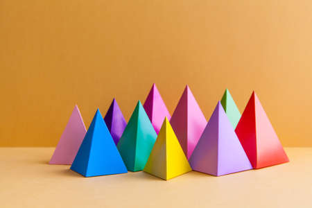 vertices: Colorful abstract geometric figures still life. Three-dimensional pyramid prism rectangular cube on orange background. Yellow blue pink green violet red colored objects. Stock Photo