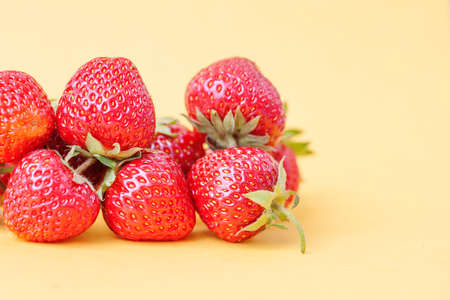 Juicy organic strawberries on yellow background. Macro view, shallow depth field photo