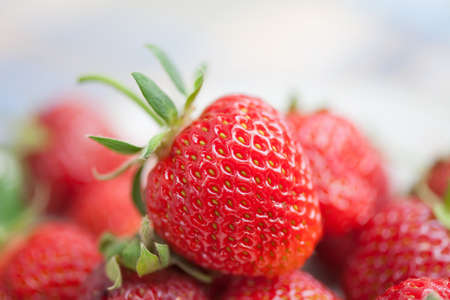 Beautiful strawberry background. Macro view red fresh berry with green leaf. Shallow depth of field photography.
