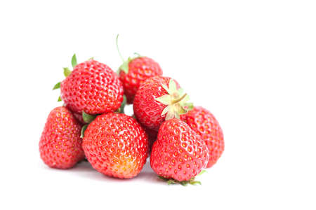Fresh ripe strawberries on white. Red fresh berries, green leaves close-up. Shallow depth of field photography.
