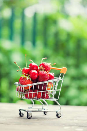 Shopping cart full of ripe red strawberries. Summer harvest on greenery background, Shallow depth field, selective focus, vertical photo.