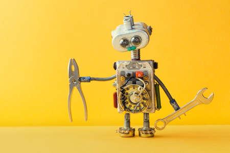Handnuts trekt robot handyman op gele achtergrond. Cyborg speelgoed lamp gloeilamp ogen kop, elektrische draden, condensatoren vintage weerstanden