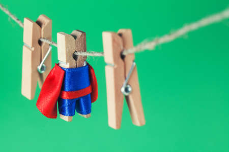 Brave superhero wooden clothespins. Team leader character in blue suit red cape. green background, selective focus. Stock Photo