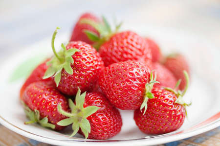 Beautiful strawberries on plate. Red fresh berries with green leaves. Shallow depth of field photography, macro view