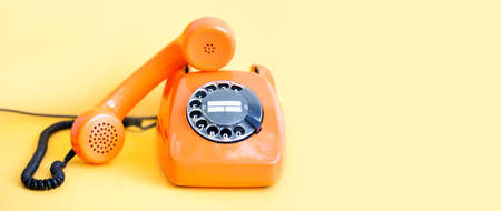 Vintage phone busy handset receiver on yellow background. Retro style orange telephone communication call center concept. Shallow depth field. copy space template. Stock Photo