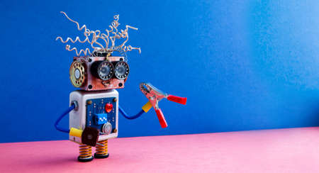 Crazy robot handyman red pliers hand. Funny toy cyborg electric wires hairstyle, big eye glasses, electronic circuit body, red heart. Blue pink background. copy space.