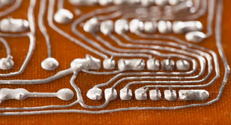 Vintage circuit board with soldering trace. Backside brown electronic chip retro style design. Macro view, shallow depth of field. Stock Photo
