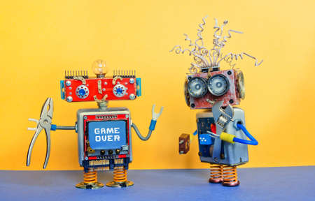 Industry 4.0 service repair maintenance concept. Creative design robotic toys, adjustable spanner silver pliers tools. Funny face robot, message Game over. Yellow blue background. Stock Photo