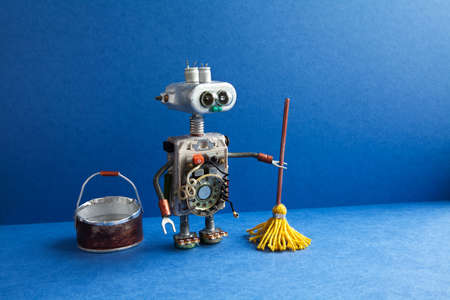 Cleaning washing room service concept. Robot cleaner with yellow mop, bucket of water, sweeping floor. Creative design toy cyborg in blue apartment