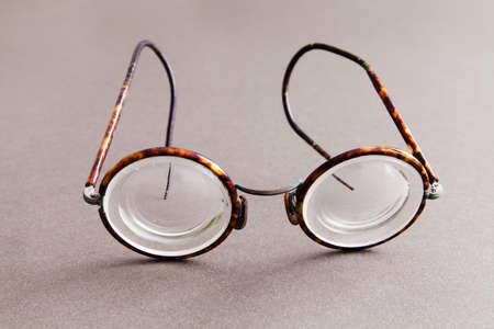 Old fashion design spectacles eyeglasses on gray paper background. Vintage style men fashion accessories. Macro view, shallow depth of field, soft focus