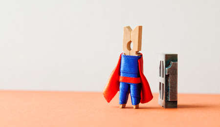 Champion superstar hero won first place. Successful leadership conceptual photography. Brave wooden clothespin superhero character and vintage letterpress digit, copy space. Stock Photo