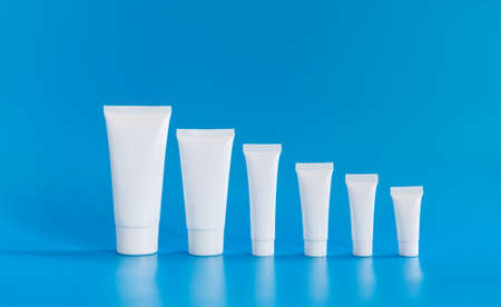 White cosmetic tube collection arranged small large on blue background. Abstract plastic containers different size capacity, blank template packaging design. copy space photo