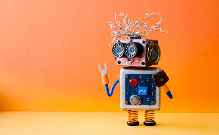 Życzliwa szalona robot złota rączka na pomarańczowym tle. Kreatywny projekt zabawka cyborga. Skopiuj zdjęcie w przestrzeni.