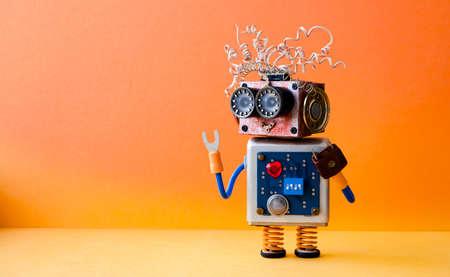 オレンジ色の背景にフレンドリーな狂ったロボット便利屋。創造的なデザインのサイボーグのグッズ。コピー スペースの写真。 写真素材