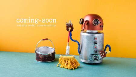 Sitio web en construcción Página de plantilla próximamente. Robot lavadora con trapeador y cubo de agua, naranja pared verde suelo interior.