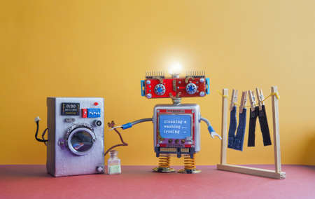 Robot automation laundry room. Robotic washer with message Cleaning, washing, ironing. Silver washing machine, mens jeans pants dried on clothesline with clothespins. yellow wall interior, red floor. Funny toys creative design 免版税图像