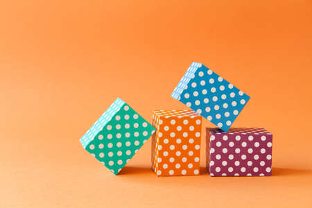 Abstract colorful geometric background vivid polka dots pattern cube boxes. Violet blue green rectangular block composition on orange paper background. Shallow depth of field. Stock Photo
