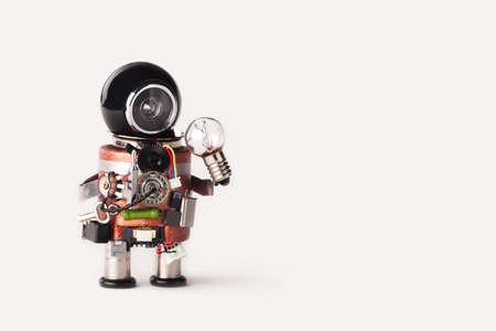 Creative idea inspiration concept. robot handyman with lamp bulb. Creative design cyborg toy, funny black helmet head. Copy space, white background.
