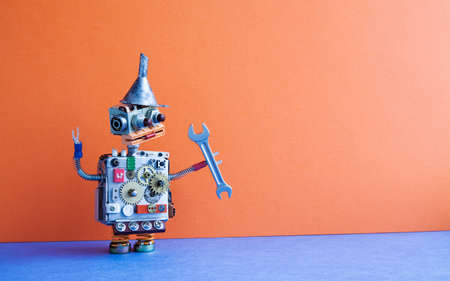 Robot handyman with hand wrench. Fixing maintenance concept. Creative design toy metal funnel hopper, cogs wheels gears metallic body. Orange wall, blue floor background. Copy space.