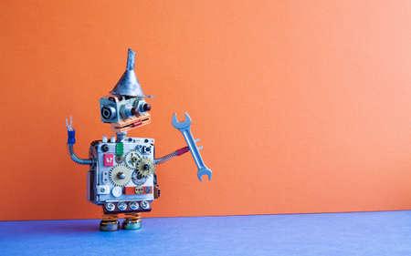 Złota rączka robota z kluczem ręcznym. Naprawa koncepcji konserwacji. Kreatywny projekt zabawkowy metalowy lejek lejkowy, koła zębate koła zębate metalowy korpus. Pomarańczowa ściana, niebieskie tło podłogi. Skopiuj miejsce. Zdjęcie Seryjne