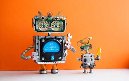 Industrie 4.0-Konzept. Großer IT-Spezialroboter mit Handschlüssel und kleinem Cyborg-Roboter. Willkommen zur neuen wirtschaftlichen Zukunftsmeldung auf blauem Display. Orange Wandhintergrund.