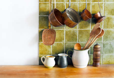 Retro kitchen still life interior. Brass utensils, chef accessories. Hanging copper kitchenware set. Pots, stewpots coffee maker, spoon, skimmer. Different sizes, pitchers on the wooden table. Copy space.