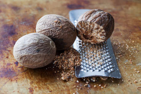 Making nutmeg powder process. Nuts silver grater. Kitchen still life photo. Shallow depth of field, aged brown rusty background. Selective focus. Standard-Bild