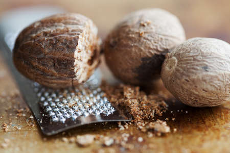 Making nutmeg powder process. Nuts silver grater. Kitchen still life photo. Shallow depth of field, aged brown rusty background. Selective focus. Stock Photo
