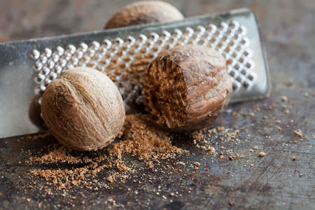 Making nutmeg powder process. Nuts silver grater. Kitchen still life photo. Shallow depth of field, aged brown rusty background. Selective focus. Stockfoto