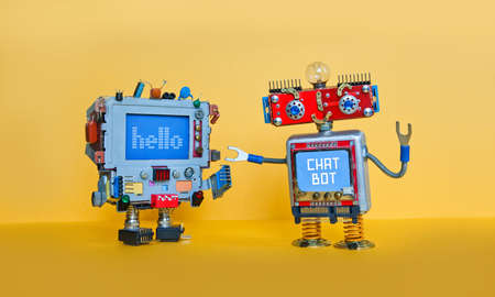Chat bot robot welcomes android robotic character. Creative design toys on yellow background. Stock Photo