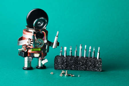 Robot handyman with different size screws. Maintenance service concept. Creative design robotic toy character, black helmet head. Macro view, shallow depth of field, greenery background.