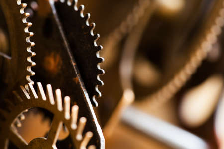 Rusty metal clock mechanism cog gears connection concept. Black iron wheels industrial still life photo. Macro view, selective focus Stock Photo