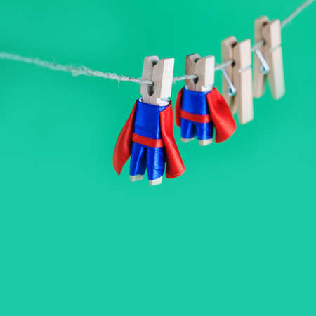 Brave superhero wooden clothespins. Team leader characters in blue suit red cape. green background, selective focus.