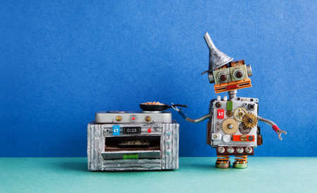 Robot chef cooking. frying pan electronic stove oven. Creative design toys, automation robotic future smart home concept. Blue wall green floor background.