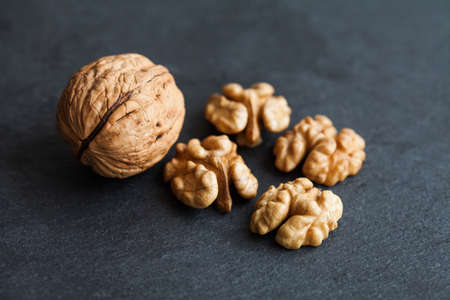 organic ripe walnut harvest on black stone background. Macro view Banque d'images
