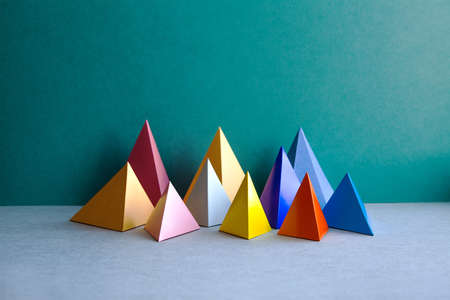 Colorful abstract geometric figures. Three-dimensional pyramid rectangular objects on green gray background. Yellow blue pink violet red colored tetrahedron Platonic solids background.