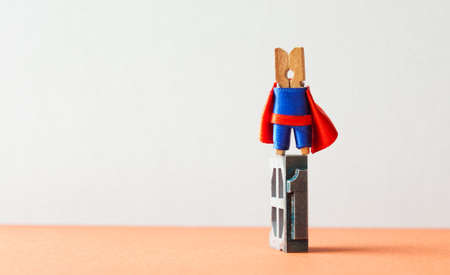 Champion superstar hero winner first place. Successful leadership conceptual photography. Brave wooden clothespin superhero character and vintage letterpress digit, copy space.