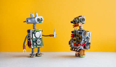 Robots on yellow background. 4th industrial revolution automation concept. Robotic serviceman with screwdriver, creative design cyborg toys. Maintenance repair fix concept Archivio Fotografico