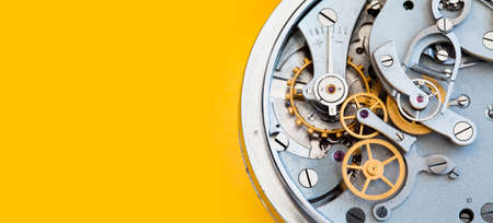 Mechanic stopwatch chronometer mechanism, spring bronze cogs wheels macro view. Shallow depth of field, selective focus. Yellow colorful background. Copy space. Stock Photo
